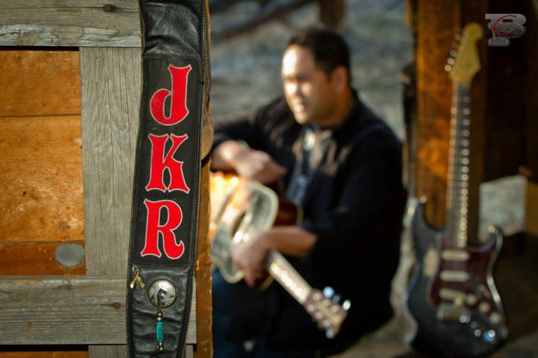 Guitarist behind the letters JKR